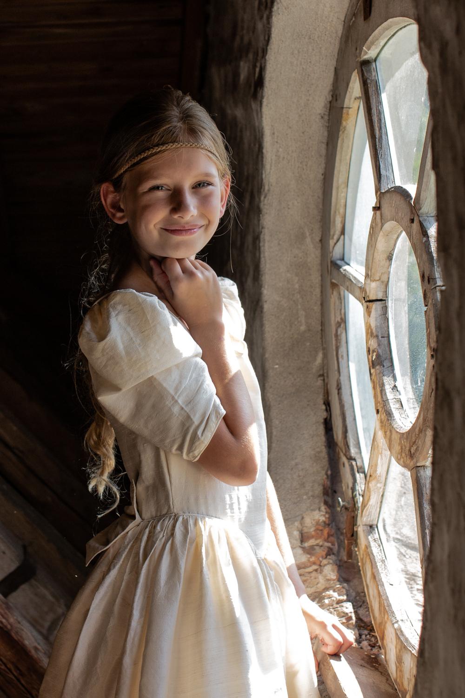 Een jonge vrouw die voor het raam staat