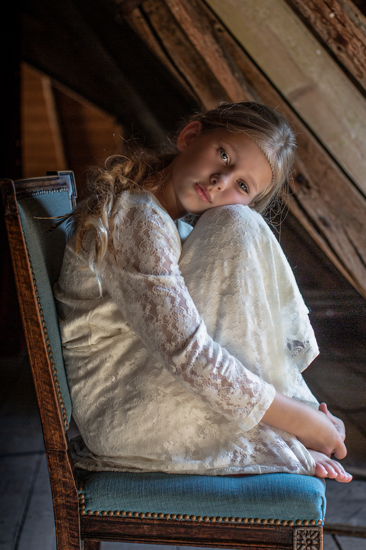 Jonge vrouw die met de knieën omhoog op stoel zit