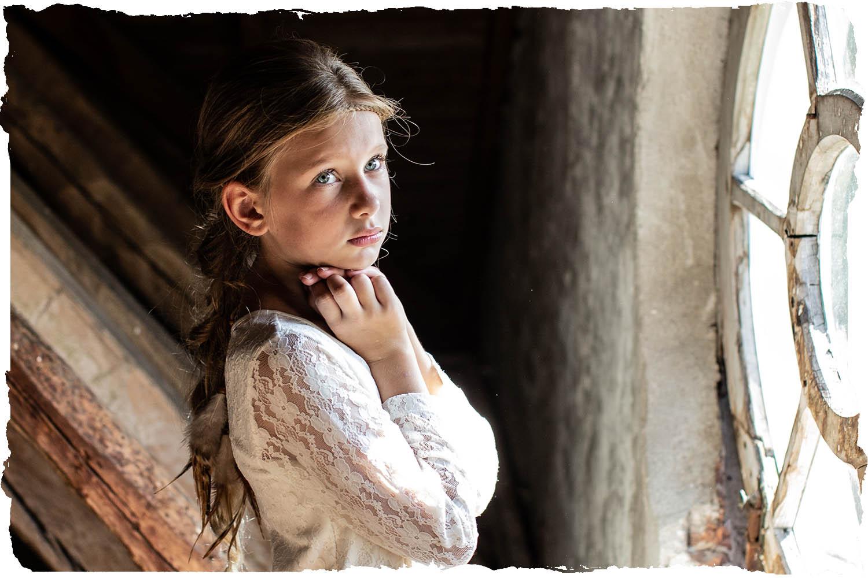 Fine art portret - een jonge vrouw voor het raam die een mooie witte jurk aanheeft met kant